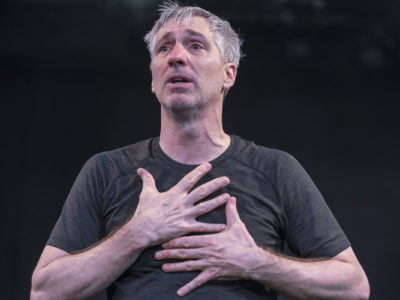 An actor in a scene: A Distressed man clutching his chest