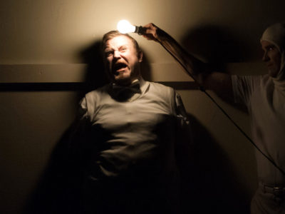 A bearded actor is presses against a wall, another actor shines a lightbulb in his face.