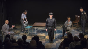 Five actors on a dark stage the central one dressed as a police officer with a shadowy audience in the forground