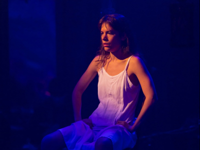 An actor sits in a spotlight on a chair, hands on her hips