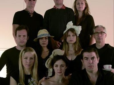 Ten actors in front of a blank wall, staring at the camera.