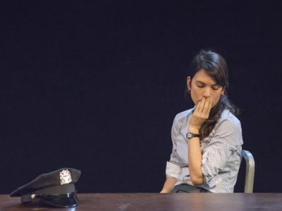 An actress in a scene: woman at a table looking worried with hand on her mouth