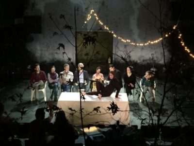 Ten actors sit onstage, on actor is on top of a table, branches and trees stand in the foreground