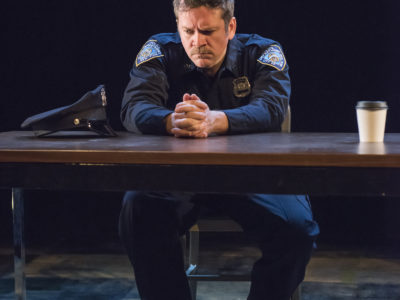 An actor in a scene: a police officer looking frustrated or worried