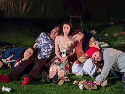 Five actors huddled together in a scene