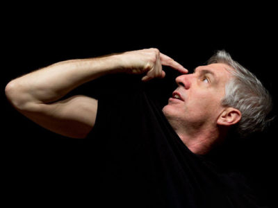 An actor in a scene: a man in black tshirt pointing at his own face with black background