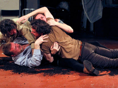 Four actors in a scene on stage: four people wrestle/struggle on a red floor covered in dirt