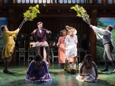 Actors leap frog across the stage while two more actors stand by holding tree branches.