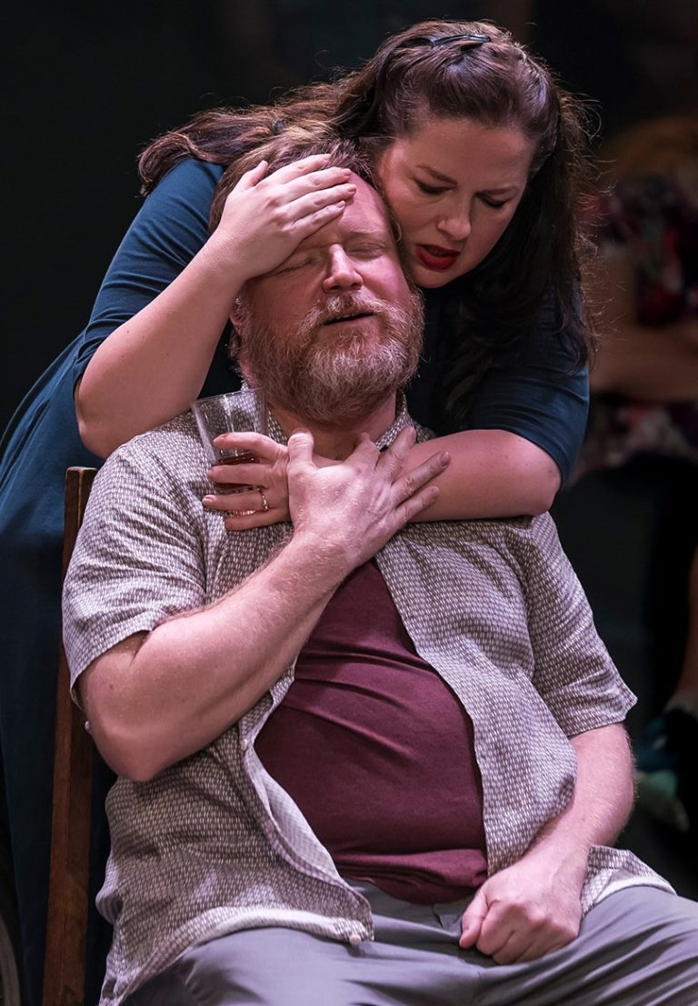 A bearded actor sitting in a chair smiling with his eyes closed, while an actress stand behind him. Her arms are wrapped around him.