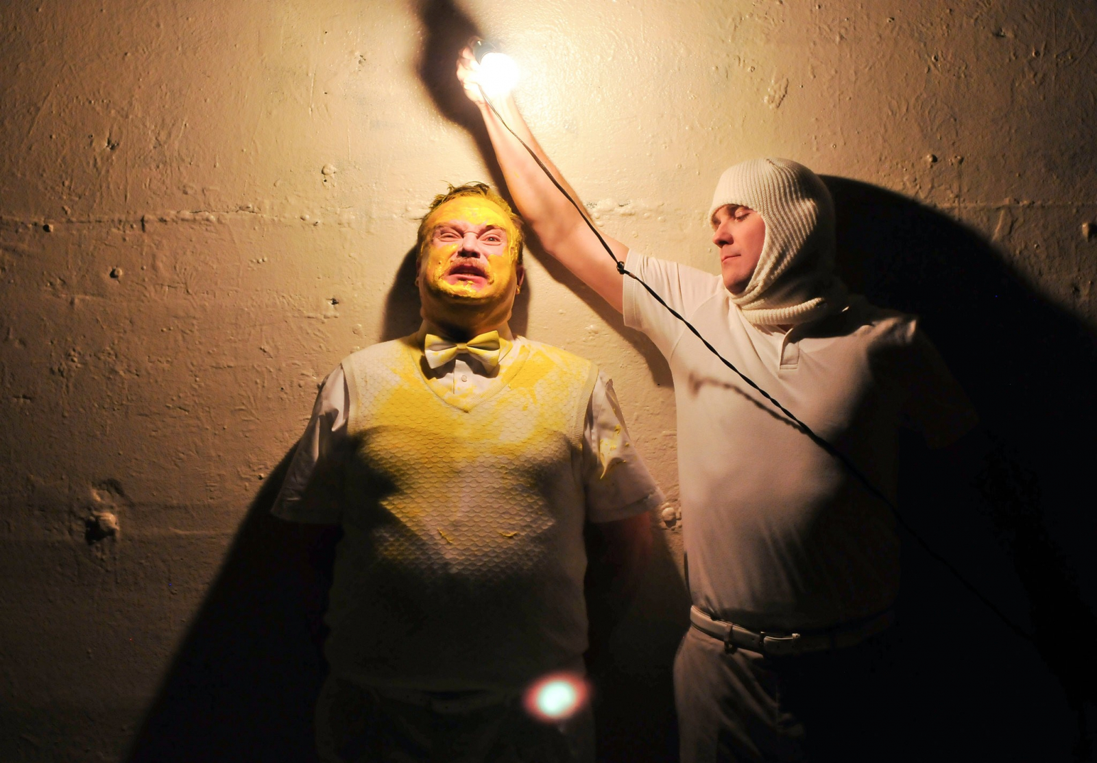 Actors, Edmund Lewis and Eric Tucker at a wall one with yellow paint on his face, the other holding a lightbulb
