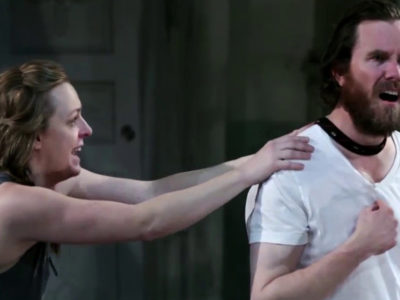 Adult female actor reaching out and touching the shoulders of adult male actor, who is pointing at his chest.