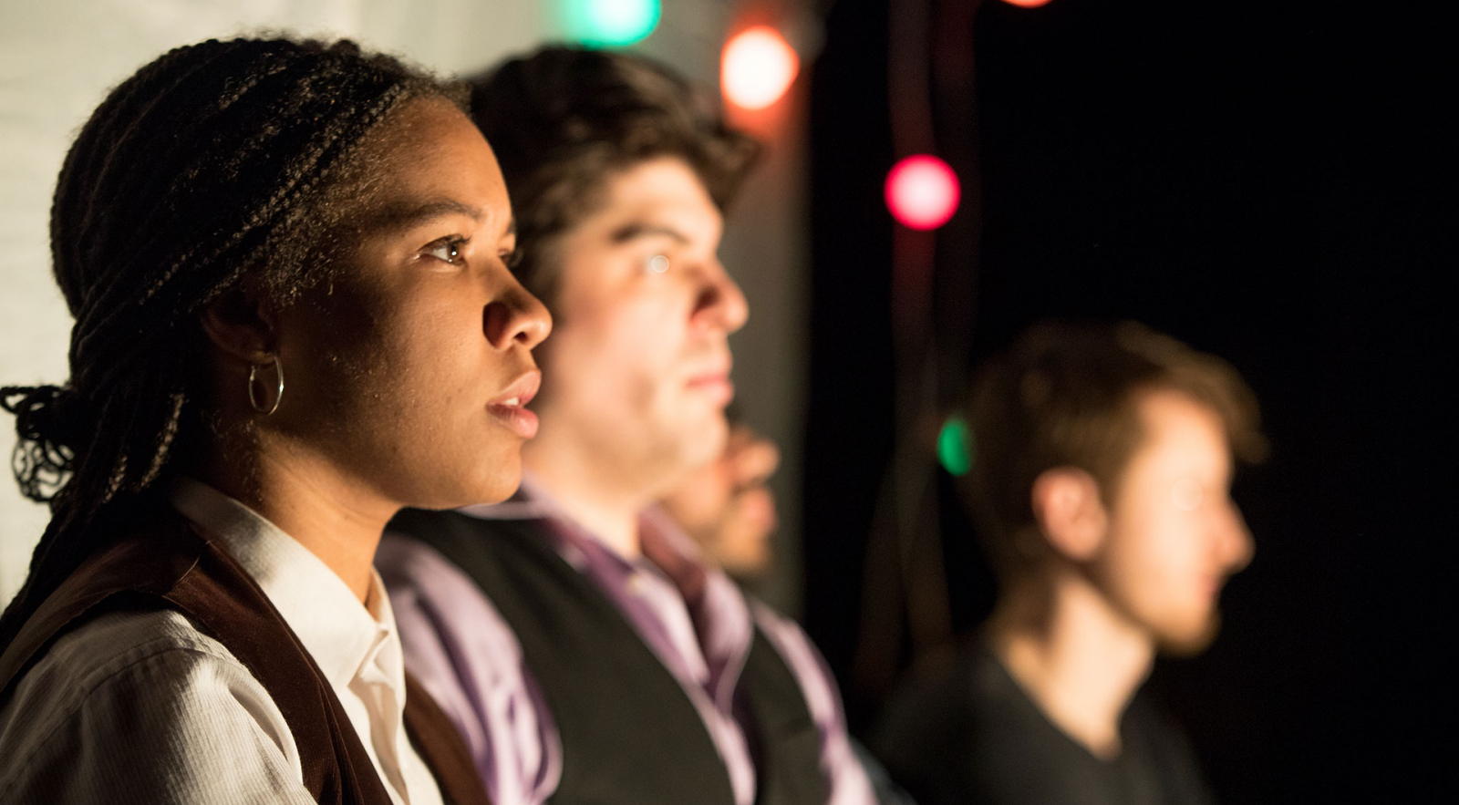 Profile faces of actors on stage with christmas lights