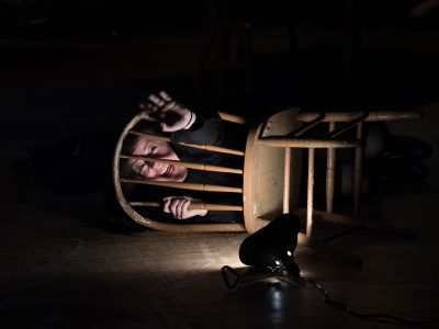 Actress trapped behind a chair with light