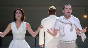 Man and woman dressed in white clothing make plea gestures with their outstretched hands