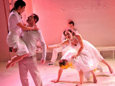 Five actors dressed in white in a chaotic scene with a pink light glowing through out