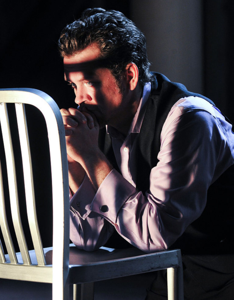 An actor in a scene: a man kneeling over a chair in prayer
