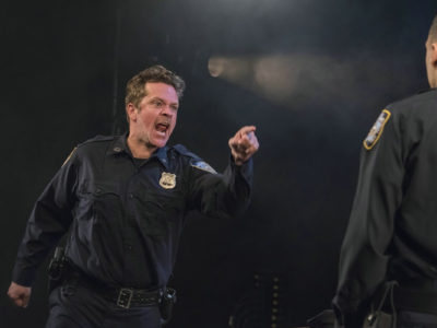 Two actors in a scene: an angry police officer yelling at another cop