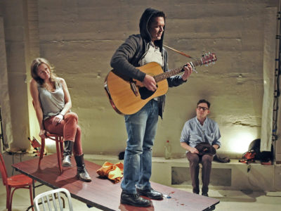 Two actors (a woman and man) on top of a long table, the man is standing and playing guitar and the woman is sitting in a chair. A third actor watches in the background.