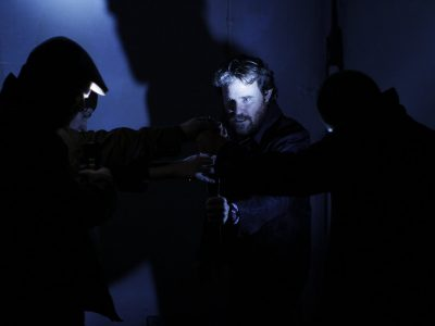 Four actors in dark setting hands all grasping a glowing indiscernible object that lights up the face of the central actor