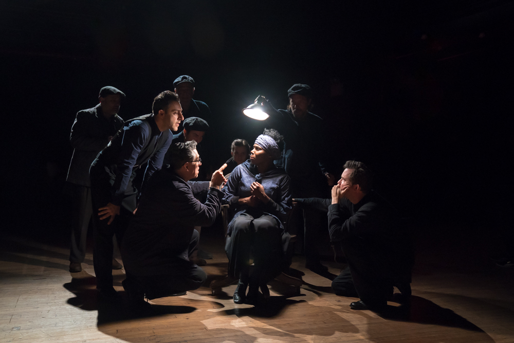 The cast of Bedlam's THE CRUCIBLE: A woman being interrogated on stage
